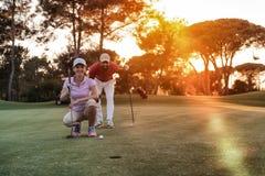 Coppie sul campo da golf al tramonto fotografia stock