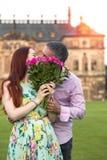 Coppie sul nascondersi baciante della data dietro il mazzo delle rose fotografia stock libera da diritti