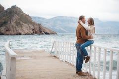 Coppie sul pilastro di legno vicino al mare in autunno fotografie stock