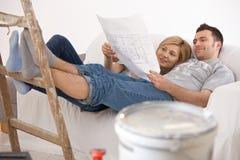 Coppie sul sofà che guarda a casa piano di rinnovamento fotografia stock libera da diritti