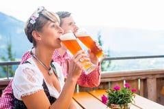 Coppie sulla birra bevente del grano della capanna della montagna Immagine Stock Libera da Diritti
