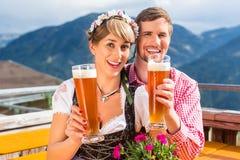 Coppie sulla birra bevente del grano della capanna della montagna Fotografia Stock