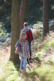 Coppie sulla passeggiata del paese attraverso il terreno boscoso Fotografie Stock