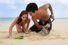 Coppie sulla scavatura della spiaggia Immagine Stock