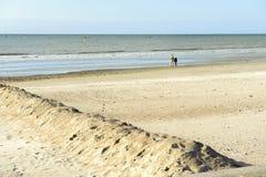 Coppie sulla spiaggia abbandonata che esamina il mare un giorno soleggiato Fotografia Stock Libera da Diritti