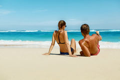 Coppie sulla spiaggia di estate Gente romantica sulla sabbia alla località di soggiorno fotografia stock libera da diritti