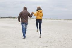 Coppie sulla spiaggia sabbiosa in autunno Fotografie Stock Libere da Diritti