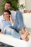 Coppie sulla telefonata del sofà Immagini Stock