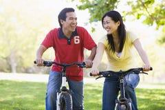 Coppie sulle bici all'aperto che sorridono Fotografie Stock Libere da Diritti