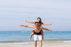 Coppie sulle vacanze estive della spiaggia, sorridere felice dei giovani, uomo Carry Woman Sea Ocean Fotografia Stock Libera da Diritti