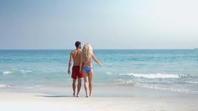 Coppie sveglie che camminano sulla spiaggia video d archivio