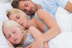 Coppie sveglie che dormono con la figlia Fotografia Stock