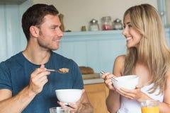 Coppie sveglie che mangiano cereale per la prima colazione Fotografia Stock