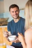 Coppie sveglie che mangiano cereale per la prima colazione Immagine Stock