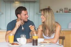 Coppie sveglie che mangiano prima colazione insieme Immagini Stock