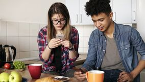 Coppie sveglie che mangiano prima colazione insieme a casa nella loro cucina, ragazza caucasica attraente e nel suo ragazzo del m stock footage