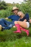 Coppie sveglie che si rilassano sull'erba Fotografia Stock