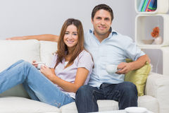 Coppie sveglie che si siedono sul sofà con le tazze di tè a casa Fotografia Stock