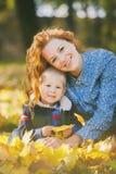 Coppie sveglie della mamma e del figlio che posano e che abbracciano nel parco di autunno immagini stock libere da diritti