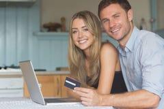 Coppie sveglie facendo uso del computer portatile insieme da comperare online Fotografia Stock