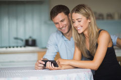 Coppie sveglie facendo uso dello smartphone insieme Immagine Stock Libera da Diritti