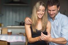 Coppie sveglie facendo uso dello smartphone insieme Immagine Stock