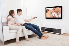 Coppie in televisione di sorveglianza del salone Fotografie Stock Libere da Diritti