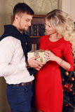 Coppie tenere in vestiti eleganti, posanti accanto all'albero di Natale a casa accogliente Fotografia Stock Libera da Diritti