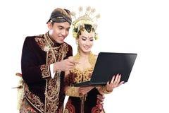 Coppie tradizionali felici di nozze di Java con il computer portatile immagini stock