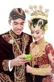 Coppie tradizionali felici di nozze di Java con il telefono cellulare Fotografia Stock Libera da Diritti