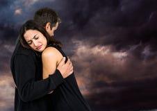 Coppie tristi che abbracciano contro il cielo nuvoloso scuro Fotografia Stock