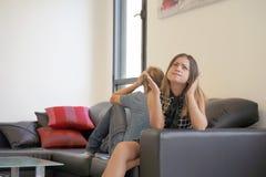 Coppie tristi dopo la discussione o disfacimento che si siede su un sofà nel salone in una casa dell'interno immagini stock