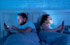 Coppie tristi e annoiate dedicate tardi ai telefoni cellulari astuti alla notte nella fase di disinteresse reciproco fotografia stock