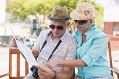 Coppie turistiche felici che esaminano mappa nella città Immagini Stock Libere da Diritti