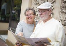 Coppie turistiche senior di divertimento che esaminano la mappa dell'opuscolo Fotografia Stock