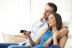 Coppie TV di sorveglianza annoiata a casa fotografia stock libera da diritti