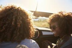 Coppie in un'automobile senza coperchio, punto di vista del passeggero posteriore Fotografie Stock Libere da Diritti