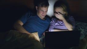 Coppie, uomo e donna, guardanti un film su un computer portatile su un letto nella camera da letto prima del letto sorveglianza d video d archivio