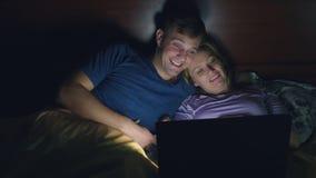 Coppie, uomo e donna, guardanti un film su un computer portatile su un letto nella camera da letto prima del letto sorveglianza d archivi video