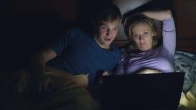 Coppie, uomo e donna, guardanti un film su un computer portatile su un letto nella camera da letto prima del letto sorveglianza d stock footage