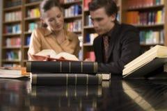 Coppie vaghe allo scrittorio delle biblioteche con il fuoco sui libri Immagini Stock Libere da Diritti