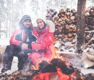 Coppie vicino al falò nel paesaggio di inverno immagine stock