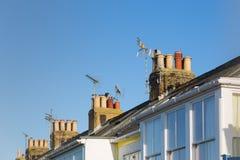 Copra le cime con i camini e le antenne sul terrazzo, case a schiera della TV Immagine Stock