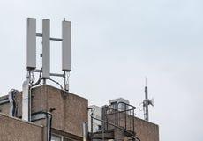 Copra le comunicazioni cellulari superiori e le antenne a microonde vedute in cima ad un edificio per uffici Fotografia Stock Libera da Diritti