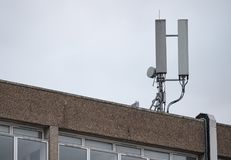 Copra le comunicazioni cellulari superiori e le antenne a microonde vedute in cima ad un edificio per uffici Fotografie Stock