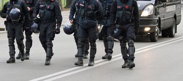 Cops while marching together in the middle of the road. During a procession of protester Stock Photo