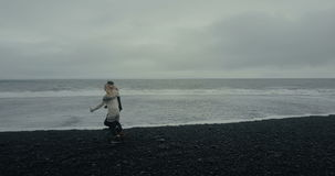 Copter που πετά κοντά στο νέο ζεύγος στο ισλανδικό πουλόβερ Άνδρας και γυναίκα που τρέχουν στη μαύρη ηφαιστειακή παραλία απόθεμα βίντεο