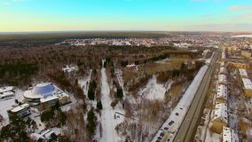 Copter flies over the winter city, near the forest. Park recreation area stock video footage