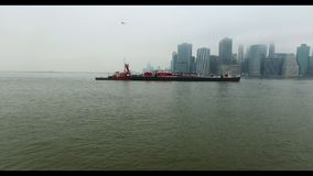 Copter flight over Hudson river. Distant view of Manhattan and ferry floating by the water stock video footage