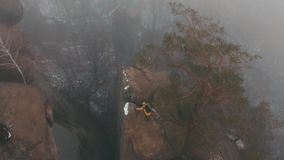 Copter fly over the rocks where man in yellow jacket climbs across the fog. Winter time.  stock video footage